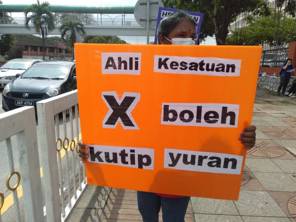 "A protestor from NUWHSAS outside Hospital Ipoh, 2 June 2020. Her sign translates to ""Union members are not allowed to collect fees"". This refers to the union membership fees, which are required for the union to continue functioning."